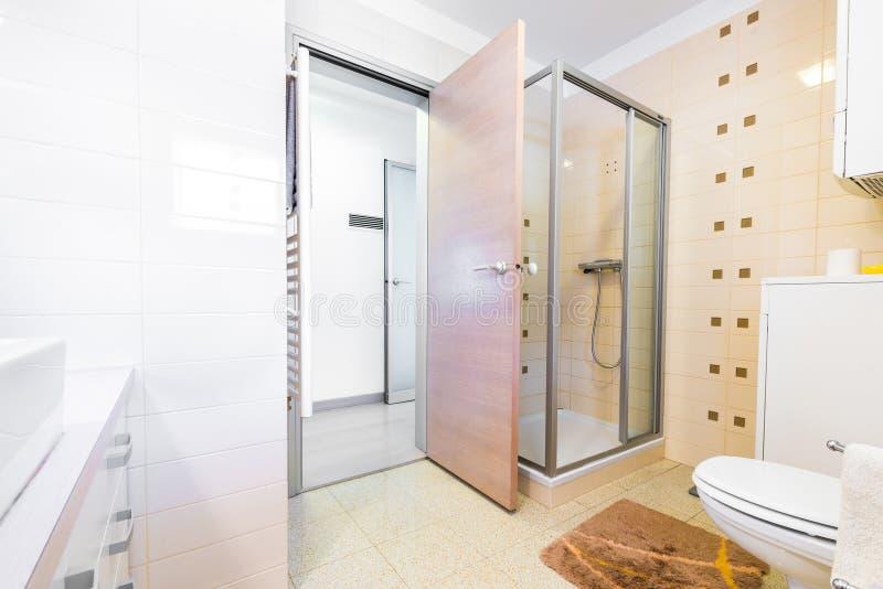 Banho pequeno moderno do hotel com chuveiro, dissipador e toalete imagem de stock