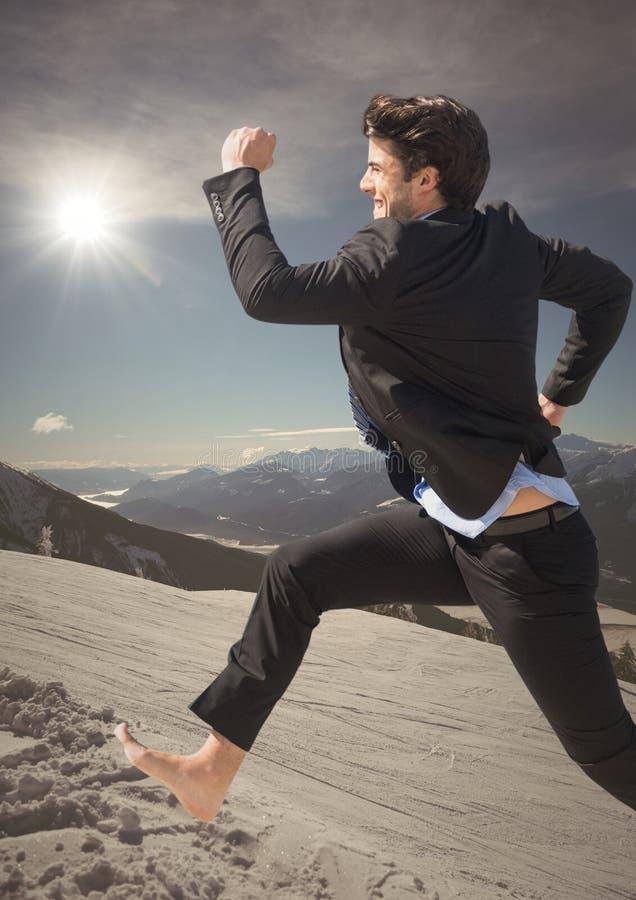 Banhoppning för affärsman på berget med solsignalljuset royaltyfri bild