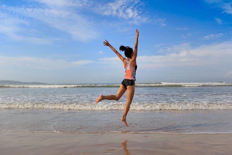 banhoppning för baddräkt för konditionkvinnakläder på stranden royaltyfria bilder