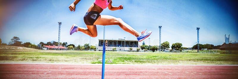 Banhoppning för kvinnlig idrottsman nen ovanför häcken arkivfoton