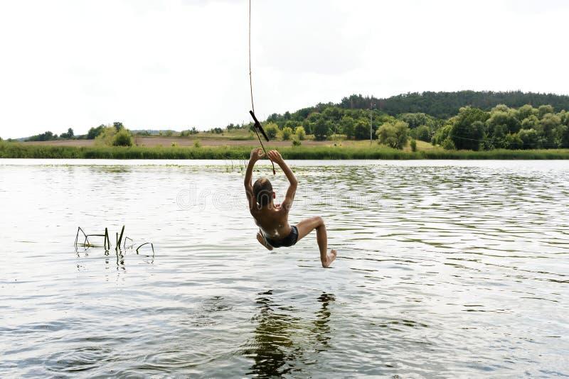 Banhoppning f?r ton?rs- pojke i floden fr?n det sv?ngande repet p? solig sommardag royaltyfri fotografi