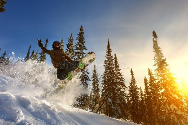 Banhoppningsnowboarderen på snowboard i berg skidar in semesterorten royaltyfria foton