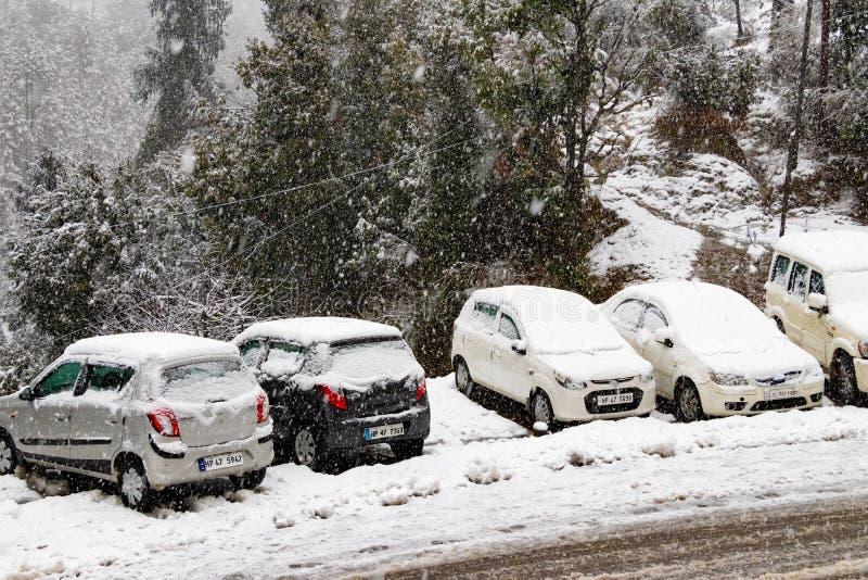 Banikhet, Dalhousie, Himachal Pradesh, India - Januari 2019 De gevolgen van zware sneeuwval, de weg en de geparkeerde auto's zijn stock afbeelding
