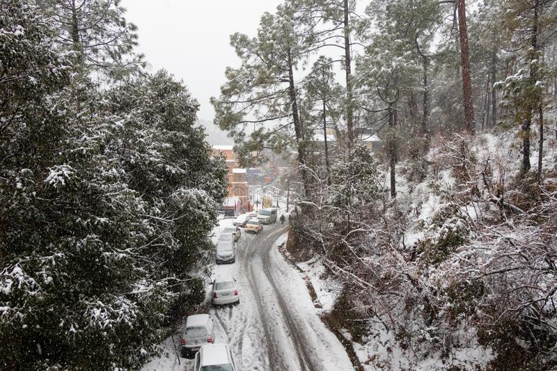 Banikhet, Dalhousie, Himachal Pradesh, India - January 2019. Consequences of heavy snowfall, the road and parked cars are covered stock photography