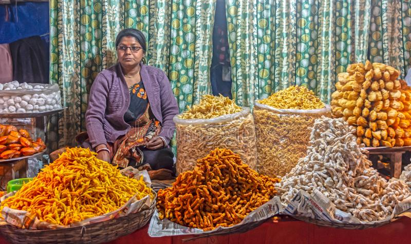 Indian woman selling different types of traditional Indian namkeen and savory snacks on the local market royalty free stock photos