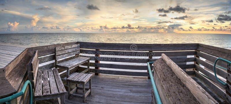 Bank übersieht den Ozean an Vanderbilt-Strand bei Sonnenuntergang stockbilder