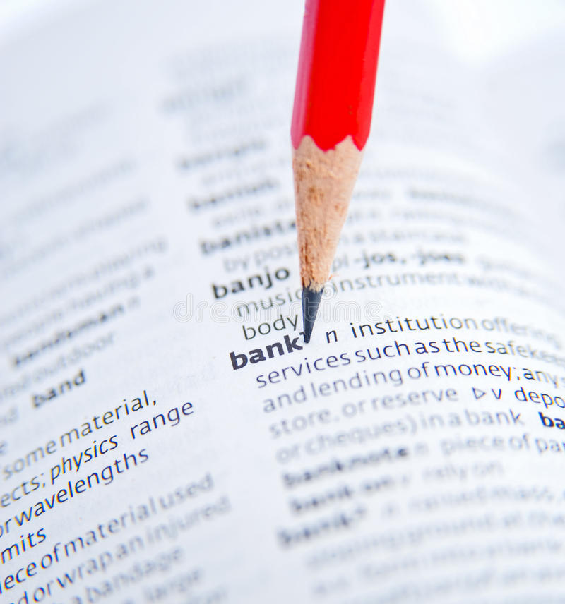 Bank. The word bank in a dictionary shown by capturing a macro shot with selective focus and further emphasized by a sharpened red pencil pointing to the word royalty free stock photo