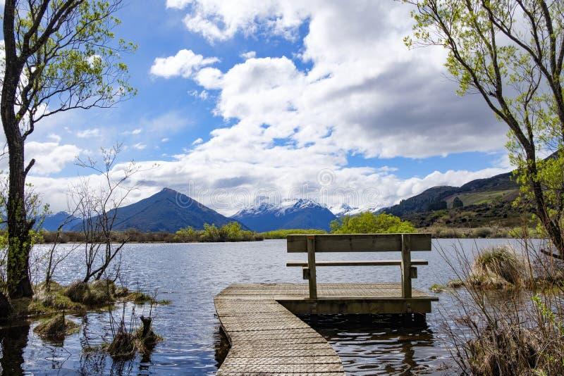Bank aan het eind van een promenade door een meer in Zuideneiland, Nieuw Zeeland stock afbeelding