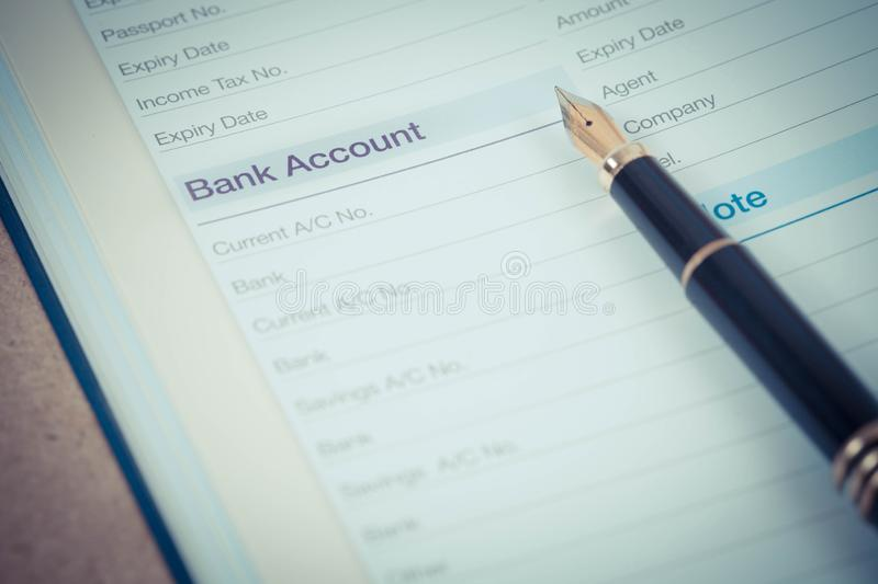 Bank account in book note with fountain pen. In color royalty free stock photo