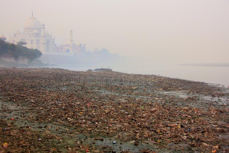 Bank av den Yamuna floden som täckas med avskräde och Taj Mahal i en dimma arkivbilder
