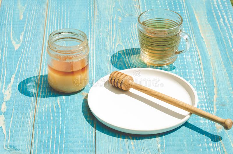 Bank av honung med den genomblöta skeden i en platta och en exponeringsglaskopp te p? en bl? tr?tabell arkivbilder