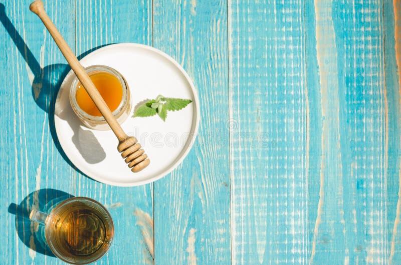Bank av honung med den genomblöta skeden i en platta och en exponeringsglaskopp te p? en bl? tr?tabell Utrymme f?r b?sta sikt och royaltyfri fotografi