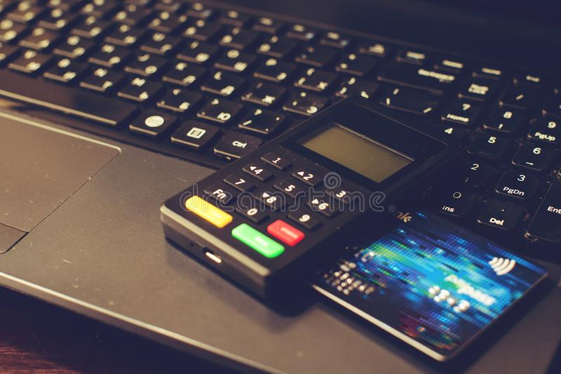 Bank card and payment device lying on keyboard, top view, toned. Image. Concept of internet crime, hacking, cyber crimes and virtual payments stock photo