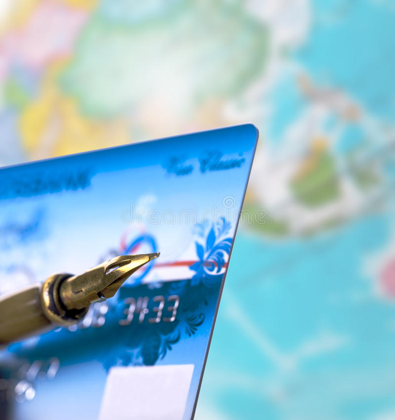 Bank card and the writing handle. Against the globe royalty free stock photography