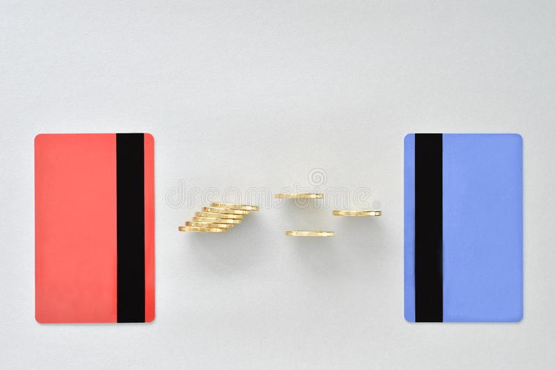 Bank cards are in the colors of living coral and blue with shiny yellow coins symbolizing the electronic exchange of money royalty free stock photography
