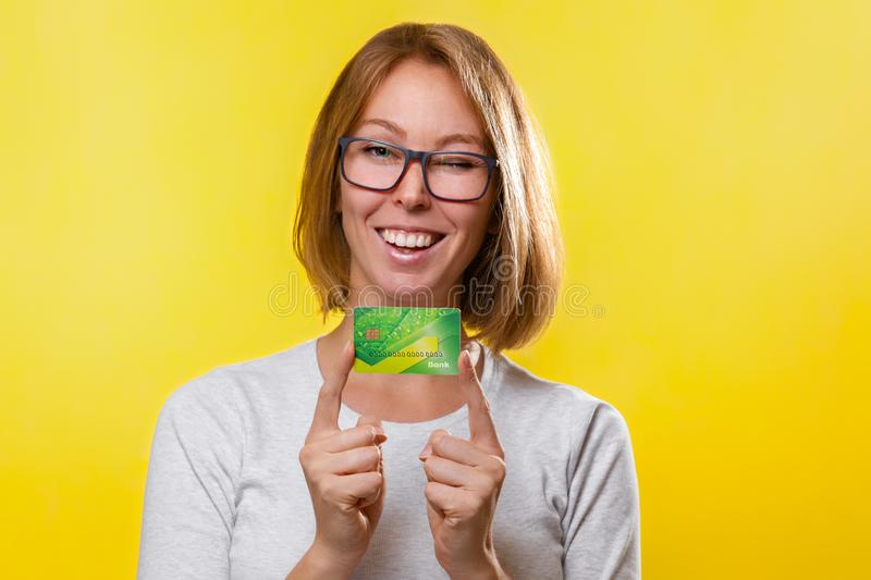 Bank cards and Finance. A young blonde woman with glasses, holding a Bank card with the index fingers of both hands. Yellow royalty free stock photos