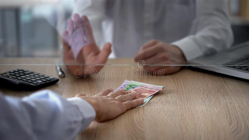 Bank cashier refusing to change euro banknotes, currency exchange limitations stock photography