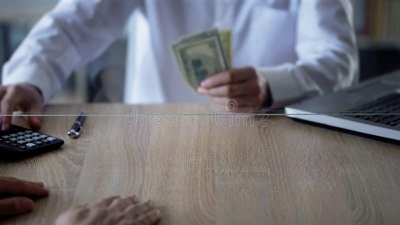 Bank clerk giving customer credit in dollars, business growth, deposit, savings stock photos
