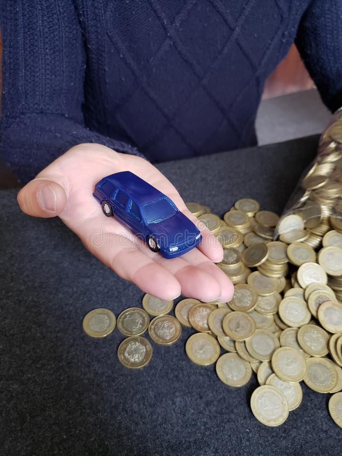 hand of a person with a blue car and savings in mexican pesos royalty free stock photo