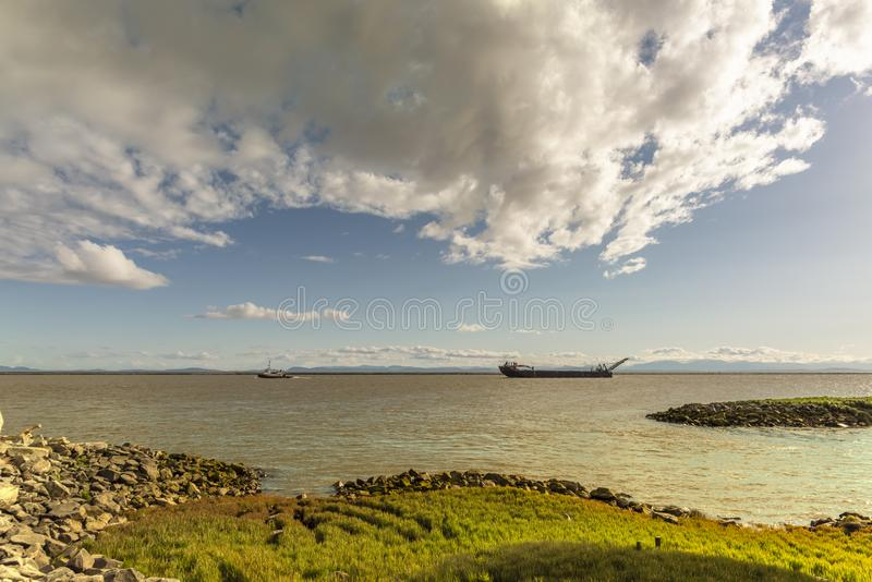Bank covered with grass and stones on the river with a boat towing a barge. A view from the bank covered with grass and stones on the river with a boat towing a stock photos