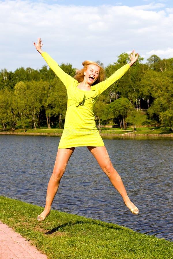 bank dziewczyny skoki rzeki szczęśliwi obraz stock