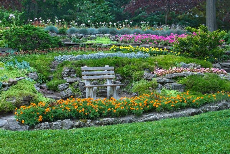 Bank in een de zomertuin met bloeiende bloemen stock foto