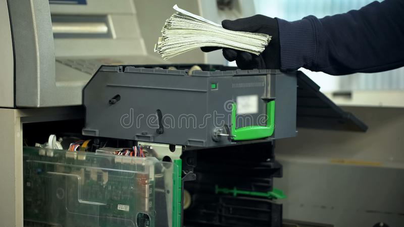 Bank employee replenishing cases of ATM with dollars currency, authorized access royalty free stock photos