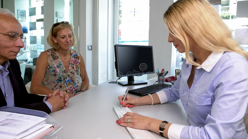 Bank employee writing check to adult clients, good service, banking system royalty free stock photo