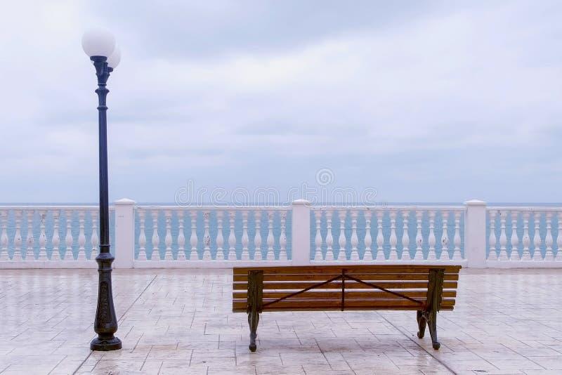 Bank en straatlantaarn op mooi terras met overzeese mening over waterkant royalty-vrije stock afbeeldingen