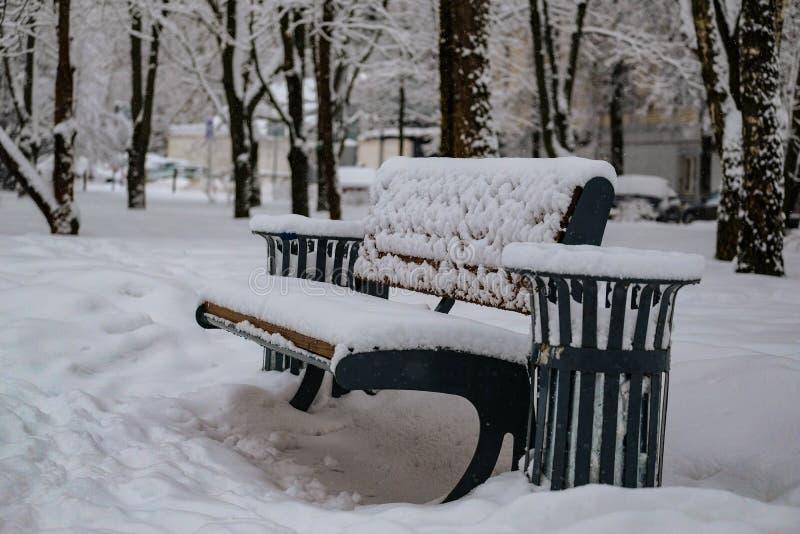 Bank en urn in een Park bij dageraad in de sneeuw royalty-vrije stock afbeeldingen