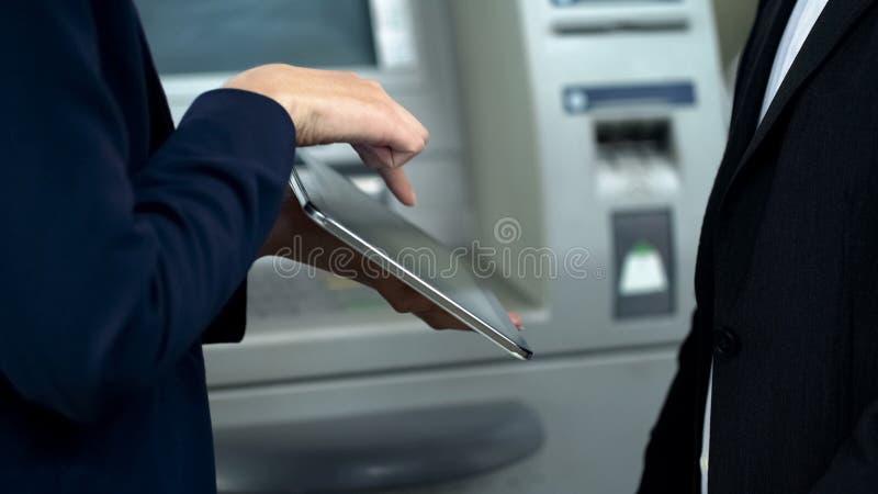 Bank hulp helpende cliënt om spoorwegkaartjes te boeken die tablet, rekeningsbetaling gebruiken royalty-vrije stock foto's