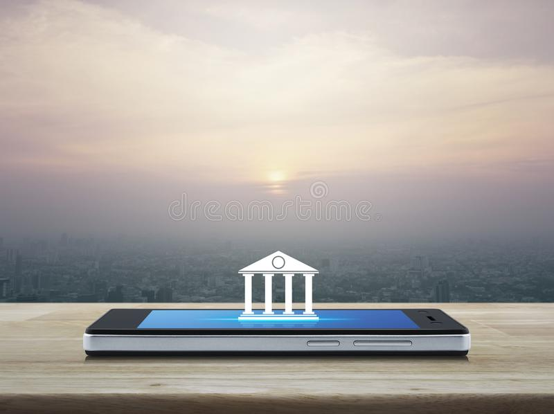 Mobile banking concept. Bank icon on modern smart phone screen on wooden table over city tower at sunset, vintage style, Mobile banking concept stock image