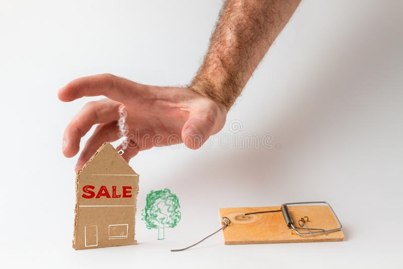 Bank investments and mortgages. Male hand reaching for the cardboard house, lying next to the trap. Text SALE. White background.  royalty free stock image