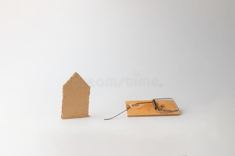 Bank investments and mortgages. Mousetrap and schematic cardboard house, on a white background. Copy space.  stock photography