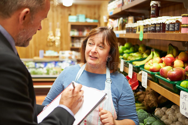 Bank Manager Meeting With Female Owner Of Farm Shop. Male Bank Manager Meeting With Female Owner Of Farm Shop stock photo
