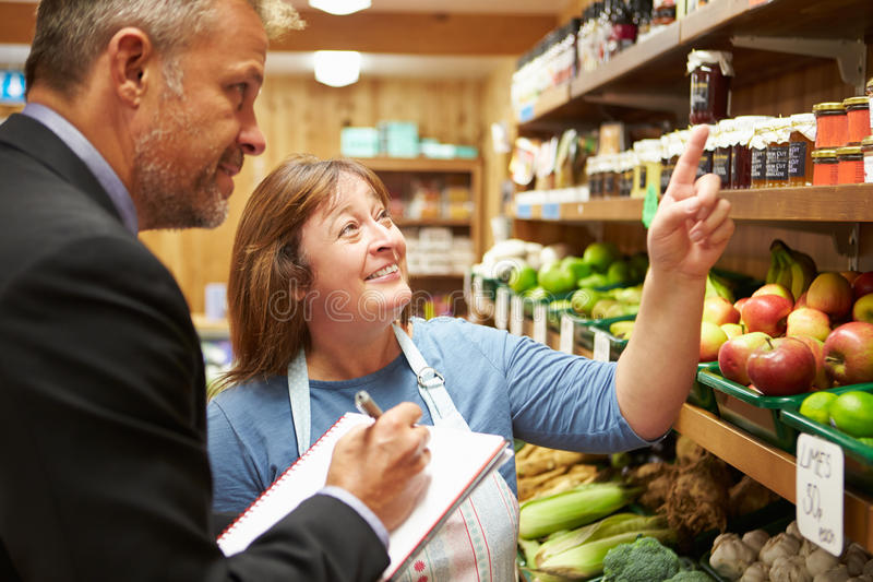 Bank Manager Meeting With Female Owner Of Farm Shop. Male Bank Manager Meeting With Female Owner Of Farm Shop royalty free stock image