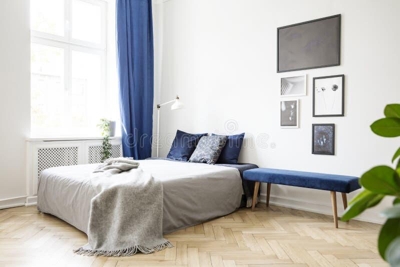 Bank naast bed met grijze deken in helder slaapkamerbinnenland met affiches en blauw gordijn Echte foto stock foto's