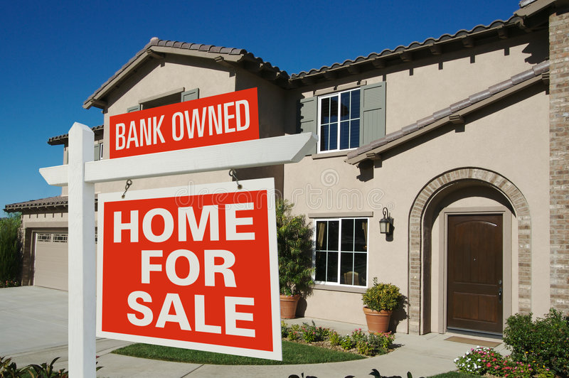 Bank Owned - Home For Sale Sign. Bank Owned Home For Sale Sign in Front of New House on Deep Blue Sky royalty free stock photo