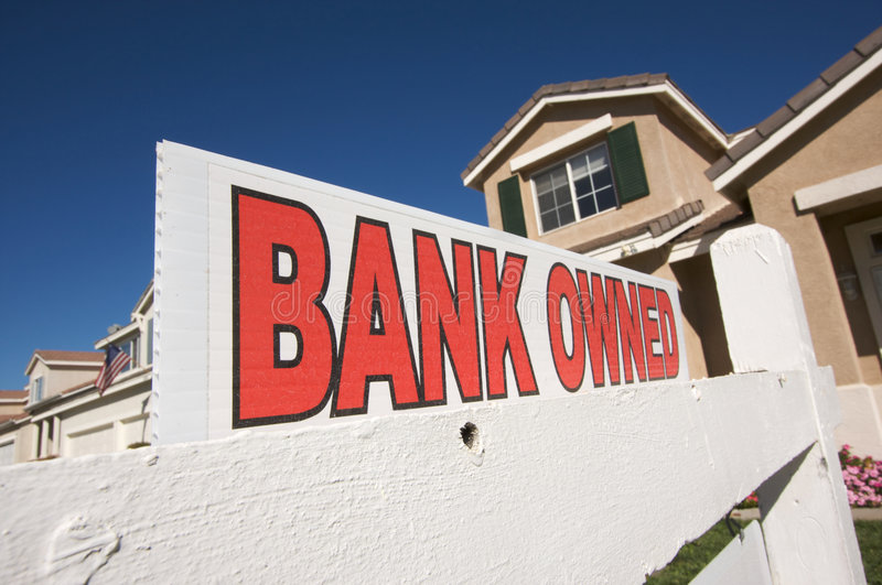 Bank Owned Real Estate Sign and House with America. N Flag in the Background royalty free stock photo