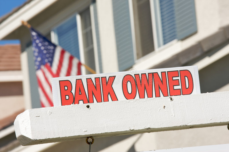 Bank Owned Real Estate Sign and House with America. N Flag in the Background royalty free stock image