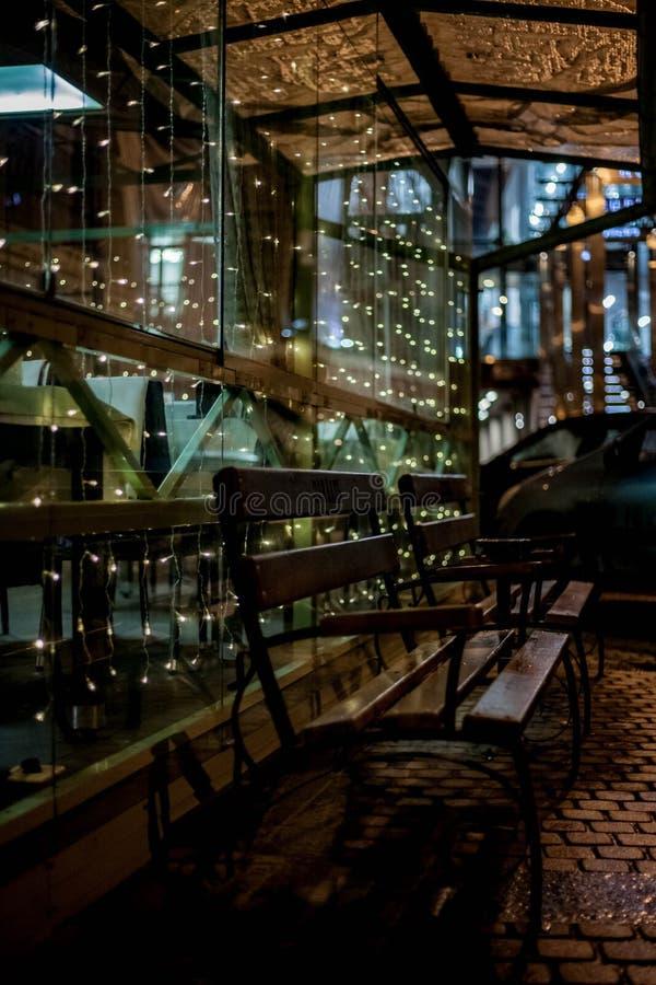 Bank, Restaurantfenster, Girlande, Lichter, Nacht lizenzfreie stockfotos
