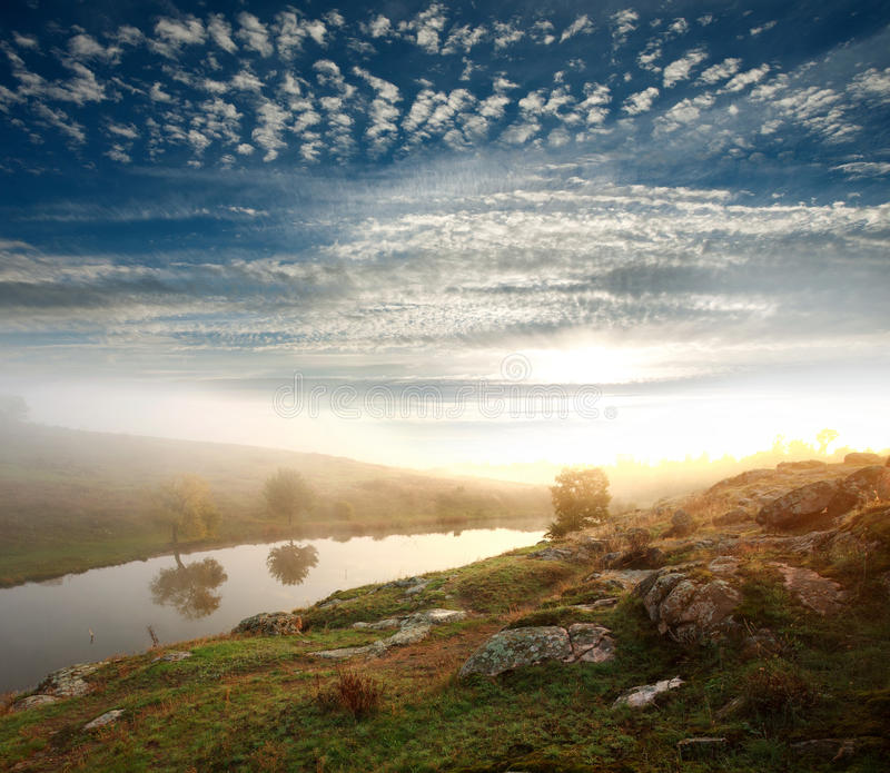 Bank of the river on the background of the rising sun. Under a blue sky with clouds royalty free stock images