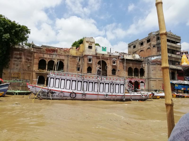On the bank of river Ganga ghat in India. A beautiful Boats floating in the river Ganga near the beautiful building on the bank of river Ganga stock photography