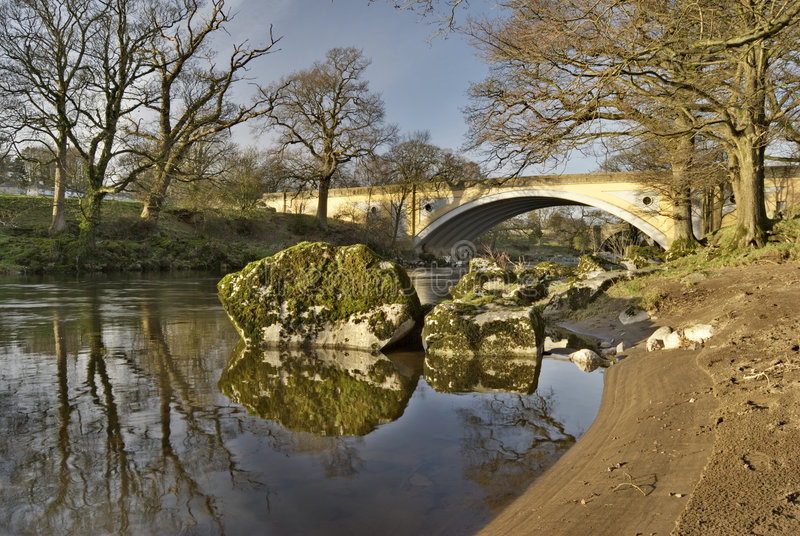 Bank of the river Lune. The sandy bank of the river Lune with the modern road bridge at Kirkby Lonsdale, Cumbria, England royalty free stock photography