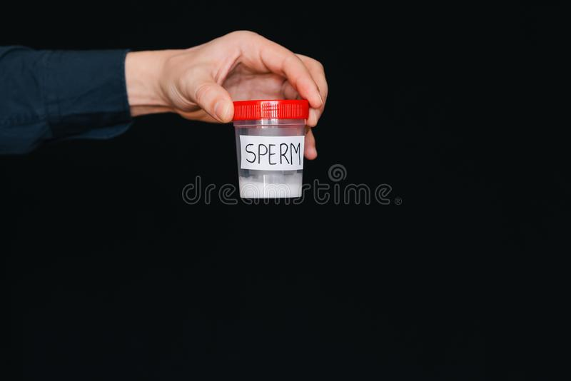 Bank of sperm in a male donor hand for analysis stock photo