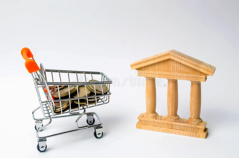Bank and the trolley with money. The concept of dividend payments, deposits in banks. Banking system, investment in the economy. Refusal of small denominations royalty free stock photos