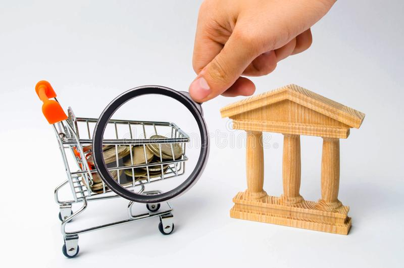 Bank and the trolley with money. The concept of dividend payments, deposits in banks. Banking system, investment in the economy. Refusal of small denominations royalty free stock photo