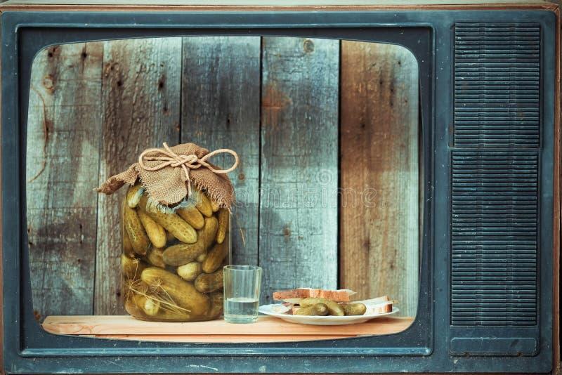 Bank van groenten in het zuur, wodka en snack in oude TV royalty-vrije stock foto