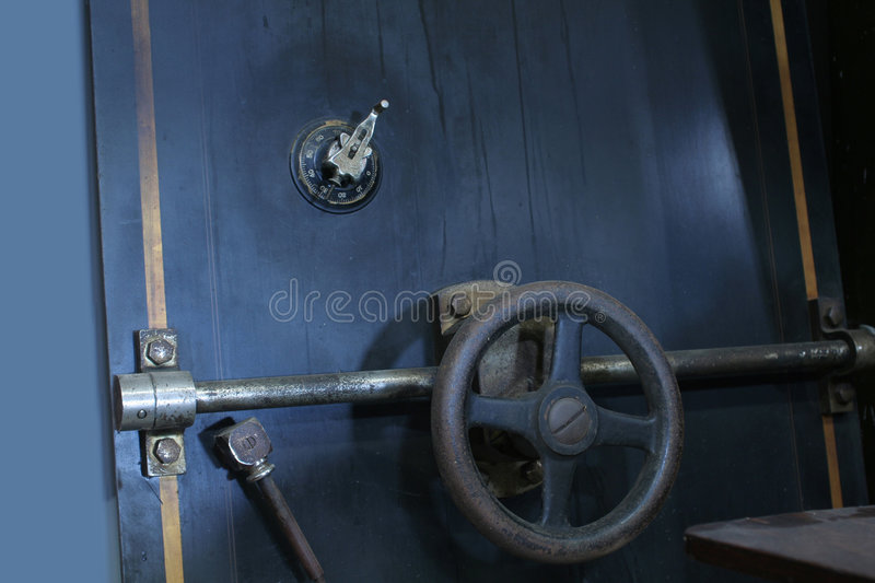 Bank Vault Door - SECURITY. Door of a bank vault with combination lock, handwheel, and lever bars. Dramatic lighting adds to scene. Metaphor for protection stock photography