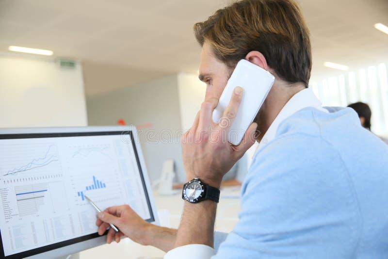 Bankaffärsman som förhandlar materiel på telefonen royaltyfri foto
